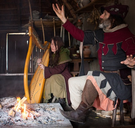 Man in medieval outfit telling a story with harpist in the background