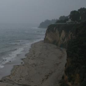 Rainy beach with cliffs