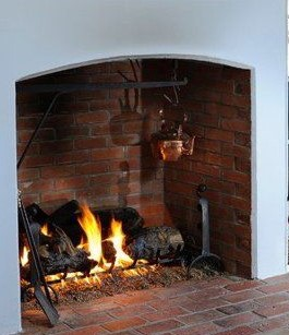 Copper kettle hanging over an open fire in a brick fireplace