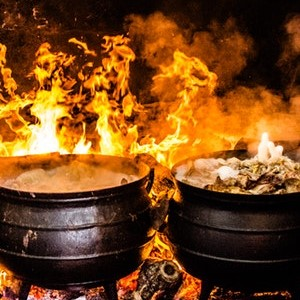 Two black cauldrons over open flames