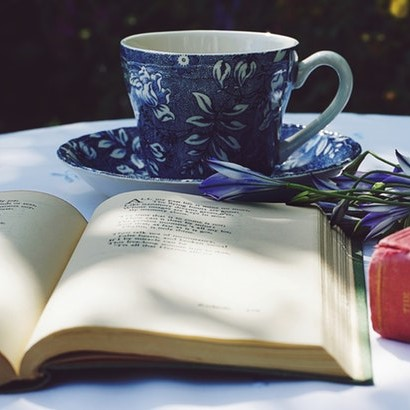 Blue floral tea cup and open book on a table