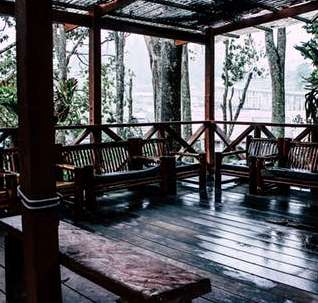 Wooden sumer house with benches in the rain