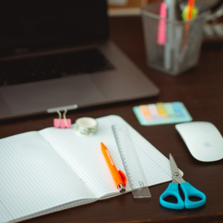 Homework supplies grid-ruled notepad, stationery and laptop