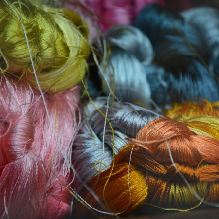 colourful pile of embroidery thread by beth-macdonald-o7Zv2-7xpNM-unsplash