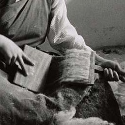 close up of a woman carding wool