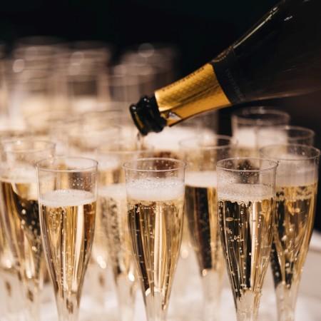 pouring a tray of champagne glasses by alexander-naglestad-xzKtOI1Cnxo-unsplash